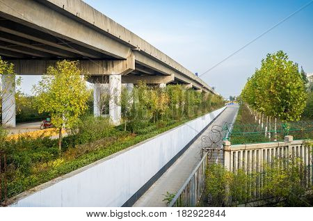Tianjin, China - Nov 1, 2016: Image captured on High Speed Rail (HSR) from Tianjin to Shanghai, passing an overhead motorway. A comfortable five-hour ride. Average speed: 300 km/h.