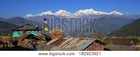 View from a village near Ghale Gaun Annapurna Conservation Area Nepal. Snow capped Manaslu range. Corn on the cob stored next to a farmhouse.
