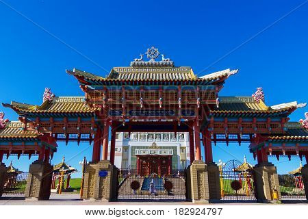 Buddhist temple Golden Tenement of Buddha Shakyamuni on a green hill against blue sky. Elista Kalmikia.