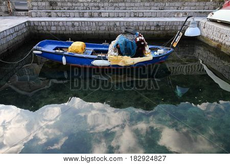 Fisherman boat with tackle and cordage at the pier clouds reflected in the water. Kotor Republic of Montenegro.