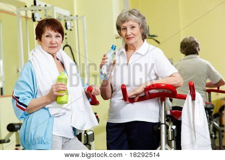 Portrait of senior females with plastic bottles looking at camera in gym