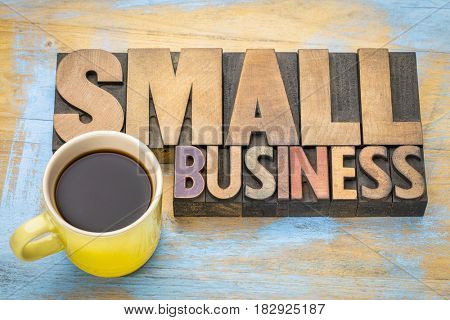 small business banner in vintage letterpress wood type blocks stained by color inks with a cup of coffee
