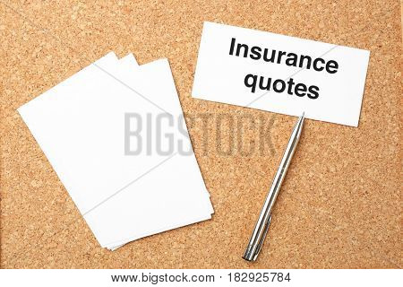 Card with text INSURANCE QUOTES, notes and pen on cork background