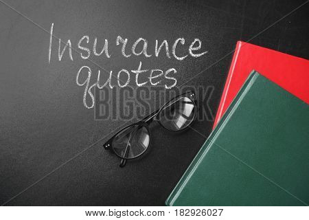 Text INSURANCE QUOTES, glasses and notebooks on blackboard background