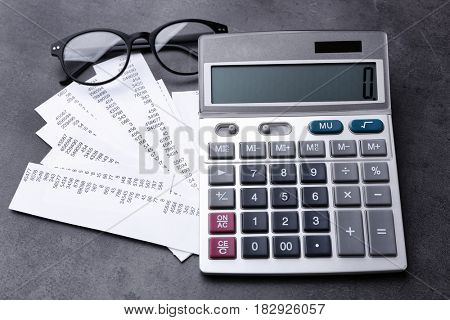 Calculator with bills on gray background. Tax concept