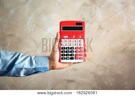 Male hand holding calculator on color background. Tax concept