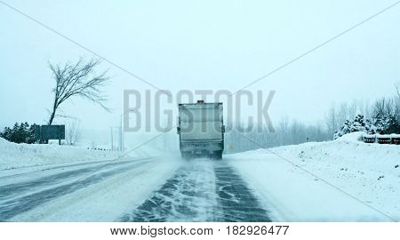 Truck in a snowstorm, pushing snow with a plow on highway and spreading salt
