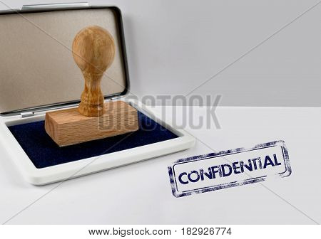 Wooden stamp on a white desk CONFIDENTIAL