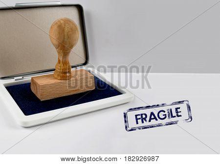 Wooden stamp on a white desk FRAGILE