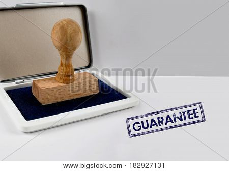 Wooden stamp on a white desk GUARANTEE