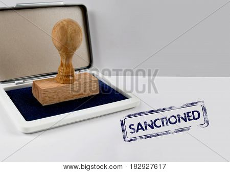 Wooden stamp on a white desk SANCTIONED