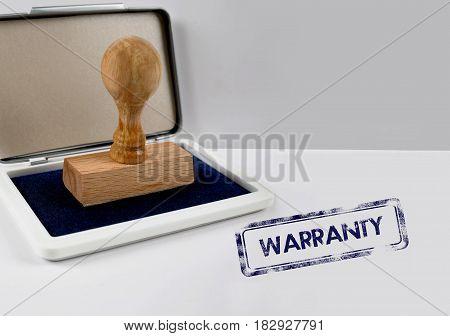 Wooden stamp on a white desk WARRANTY