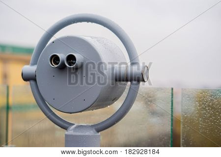closeup coin operated binoculars overlooking after rain