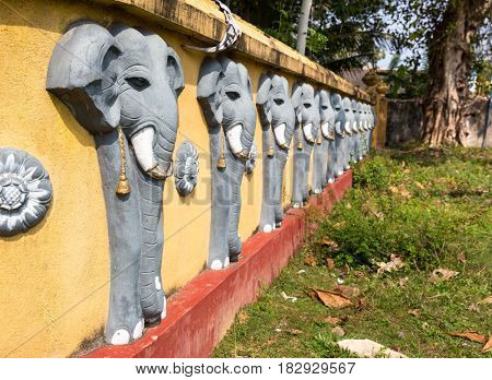 Wall with elephant sculptures in buddha temple