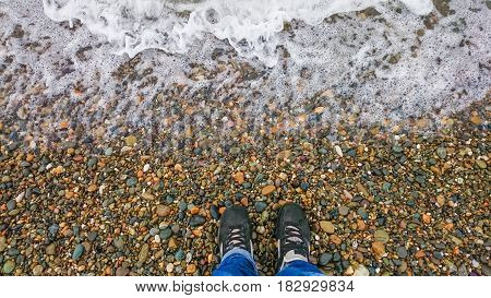 hipster in black shoes standing on a pebble beach in front of a receding wave of foam curiosity concept
