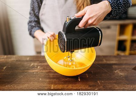 Young woman in apron whip dough in bowl with mixer