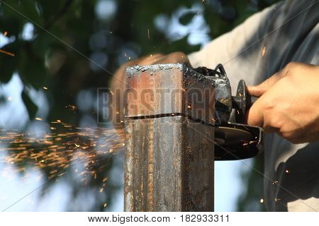 working tool cuts an iron pole outdoors