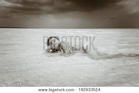 nice gorgeous view of a beautiful dreaming little girl laying, relaxing in crystal clear ocean water on sunny day against dark stormy sky background at Cayo Coco island. Cuba