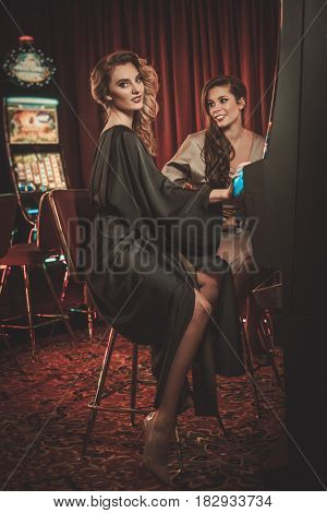 Beautiful women near slots machines in a luxury casino interior
