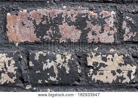 Close up of old colorful black mottled and flaking bricks that would make an artistic textured background