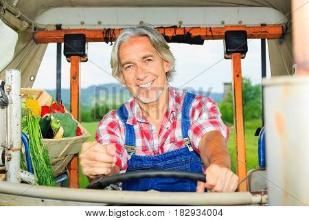 farmer driving his tractor, transporting a crate of vegetables