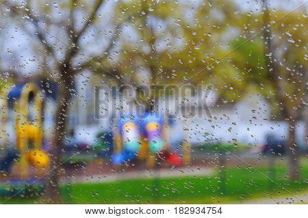 Rain Drop On Window Glass With Blur Tree Background