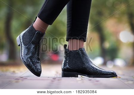 A girl steps in python leather shoes. The girl is walking in the shoes along the street