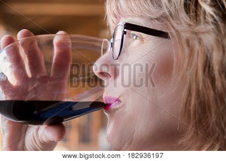 horizontal profile head shot of a caucasian woman wearing glasses taking a sip if wine from a wine glass.