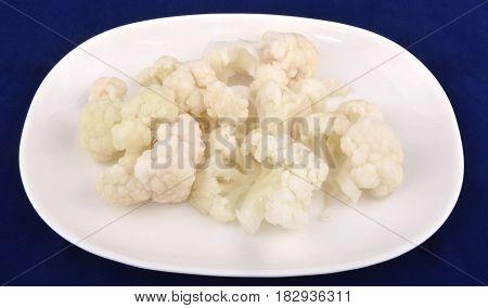 Seasonal salad of pickled cauliflower on blue background