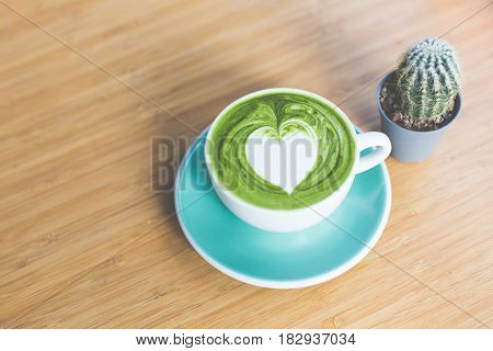 Hot Matcha Green Tea With Heart Shape Latte Art In Green Cup And Cactus On Wood Table. Love Concepti
