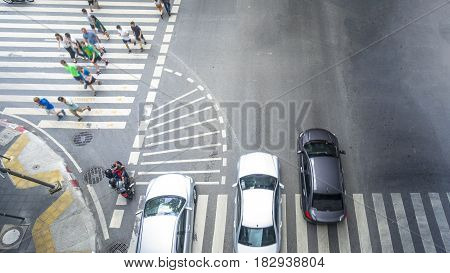 people walk on across the pedestrian crosswalk street with the transportation cars and motorcycle go pass the crosswalk junction in the city (Aerial top view)