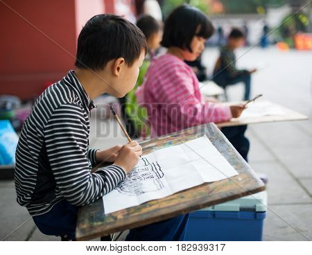 Chengdu - Pixian Sichuan Province China - Apr 12 2015: Children learning to draw in a temple