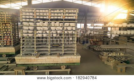 view of ceramic factory process cup production. there are ceramic arranged on shelf