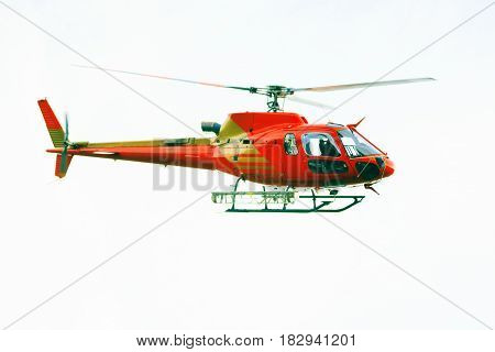 red helicopter in front of an overcast sky
