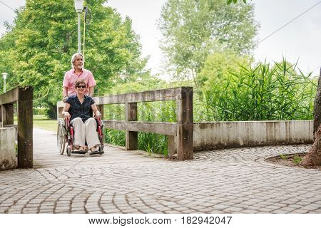Senior couple in wheelchair, enjoying a day in the park
