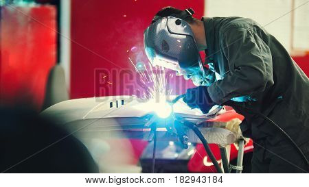 Welding industrial: worker in helmet repair detail in car auto service - blue sparklers, telephoto
