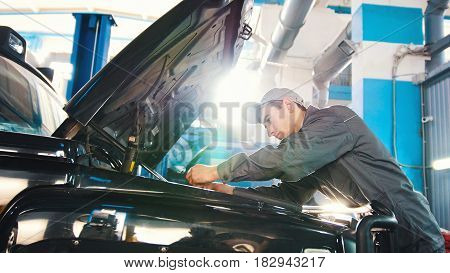 Mechanic in car service - repairing in engine compartment for luxury SUV, wide angle