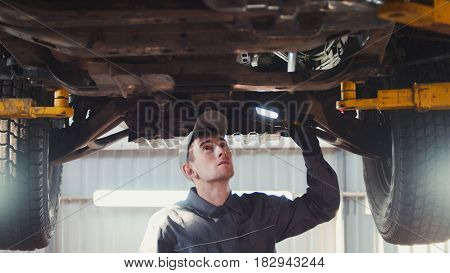 Car service - a mechanic checks the suspension of SUV, telephoto