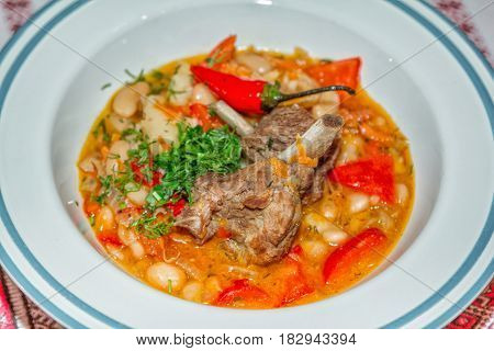 Stewed vegetables with beans and pork ribs served with chili pepper and cut dill
