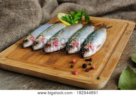 Fresh sardines. Omega 3. Fish with herbs. Mediterranean fish on the wooden carving board with pepper and lemon