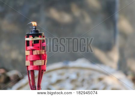 Red bamboo torch with flame traditional style blurred background.