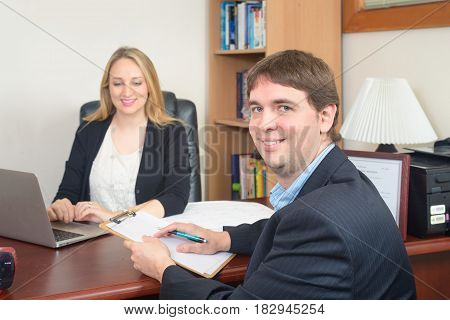 Business people - young attractive woman and successful man - talking over laptop at the table in office, smiling, looking at camera.