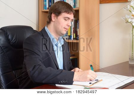 Businessman taking notes working at the table in office.