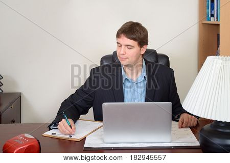 Businessman taking notes working with his laptop at the table in office.