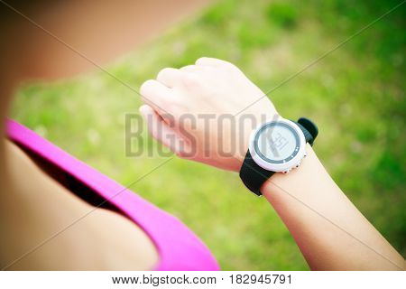 young woman jogging, checking her pulse monitor.