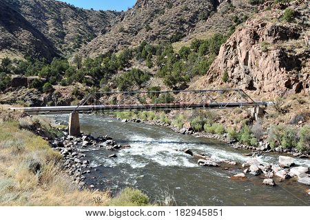 White water river flowing under a utility pipe and through Colorado's Royal Gorge