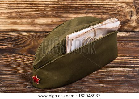 Old letters lie in a military cap with a red star on an old table