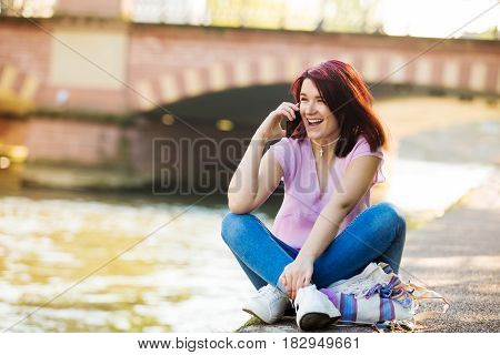 Smart phone Young smiling woman talking on mobile phone near a river in a spring day.Excited young woman talking on mobile phone near a river in FranceStrasbourg.Student.