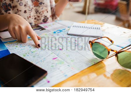 Young Tourist woman planning a travel trip with a city map.Young Woman making a travel plan for sightseeing the beautiful places of Barcelona.