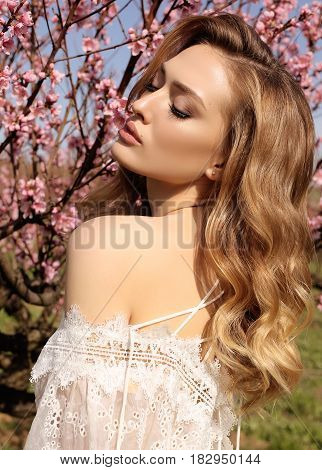 Gorgeous Woman With Blond Hair In Elegant Dress Posing In Blossom Garden